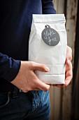Hands holding a bag of gluten free flour