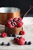 Raspberries and blueberries in a copper pot
