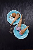 Ice cream cones with sprinkles and nuts, filled with blueberry ice cream, raspberry ice cream and caramel ice cream