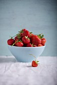Strawberries in a white bowl on a white tablecloth