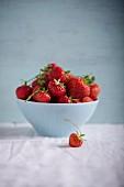 Erdbeeren in einer weissen Schüssel auf weisser Tischdecke