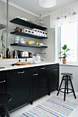 Küche mit schwarzen Unterschränken und weisser Arbeitsplatte, oberhalb schwarze Ablagen an grauer Wand