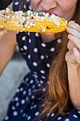 A woman eating elotes (grilled corn cobs, street food from Mexico)