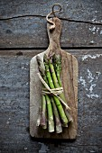 Fresh green asparagus on a rustic wooden board