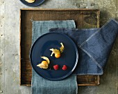 Two physallis and two raspberries on a blue plate and a wooden tray