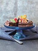 Chocolate cake garnished with fresh fruit, sliced