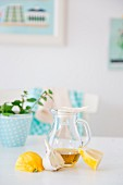 An arrangement of lemons, garlic, a carafe of olive oil and a pot of mint