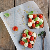 Toast topped with tomatoes, mozzarella, pesto and basil