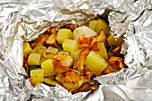 Scallops with courgettes and chanterelle mushrooms cooked in aluminium foil