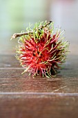A rambutan on a wooden surface