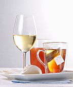 A glass of white wine, orange juice and a tea