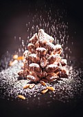 A chocolate pine cone with icing sugar and pine nuts