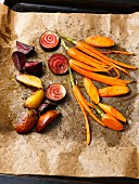 Vegan oven cooked vegetables (carrots, Jerusalem artichoke, Tonda di Chioggia) on baking paper
