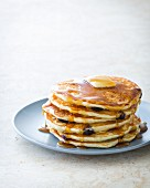 A stack of blueberry pancakes on a plate with maple syrup and butter