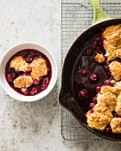 Cherry cobbler in a cast iron pan and in a bowl