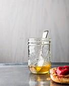 Honig im Glas mit Löffel und English Muffin mit Himbeeraufstrich