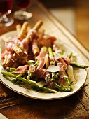 Grilled asparagus and breadsticks wrapped in Parma ham