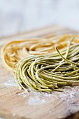 Fresh buckwheat and lupine flour pasta on wooden board