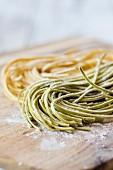 Fresh buckwheat and lupine flour pasta on wooden board