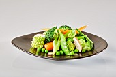 A plate of vegetables with Romanesco, broccoli, peas, spring onions, carrots, Brussels sprouts, mushrooms and mange tout