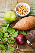 Various ingredients for oven-roasted vegan vegetables (pears, chickpeas, sweet potato, spinach, red onion, beetroot) with a knife on a wooden surface