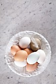 Fresh eggs on a plate with a feather (seen from above)
