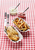 Fried chicken with chips, ketchup and remoulade on a checked tablecloth