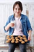 Sitzendes Mädchen mit frisch gebackenen Müslikeksen und einem Glas Milch