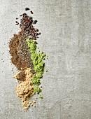 Maca-Pulver, Gerstengraspulver, Chiasamen, gemahlene Leinsamen und Kakaonibs auf grauem Tisch (Draufsicht)