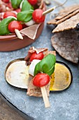 Tomato and mozzarella skewers with Parma ham and basil on crispbread