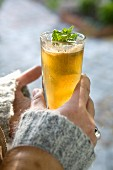 Hands holding a glass of apple juice with mint