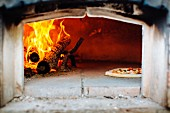 A pizza being baked in a traditional wood-fired oven