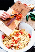 A woman adding tomatoes to a pasta salad