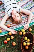 Frau auf einem Webteppich liegend, über ihrem Kopf frisch geerntete Äpfel