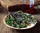 Sprigs of rosemary and thyme in a vintage bowl with a bottle of red wine in the background