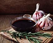 Rosemary, garlic bulbs and a bowl of balsamic vinegar