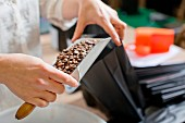 A woman filling coffee beans into a black paper bag