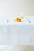 A sesame seed roll and a glass of wine on a table laid with a white cloth