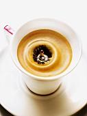Tropfen fällt in Espresso