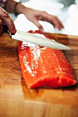 A salmon steak being dropped on a wooden board