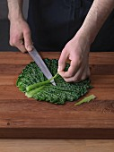 The mid-rib section being cut out of a leaf of blanched savoy cabbage