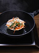 Vegetables in a bowl being steamed in a pan