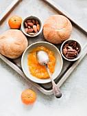 Bread rolls, jam, almonds and mandarins