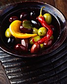 Green olives, black olives, a red chilli, an orange slice and a bay leaf in vintage bowl