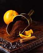 Frische Orangen und Schalen mit Zimtstange und frisch gemahlenem Kaffee in Schütte