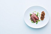 Pigeon on a bed of lentils with broad beans