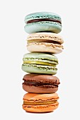 A stack of five different coloured macaroons on a white surface