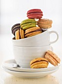 Various different coloured macaroons in a coffee cup