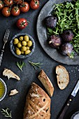 Fresh bread, olives, tomatoes, lettuce, figs and olive oil on a grey table