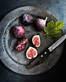 Fresh figs on a metal plate with a knife and a fig leaf (seen from above)
